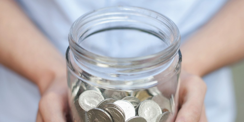 Midsection of young man holding jar full of coins