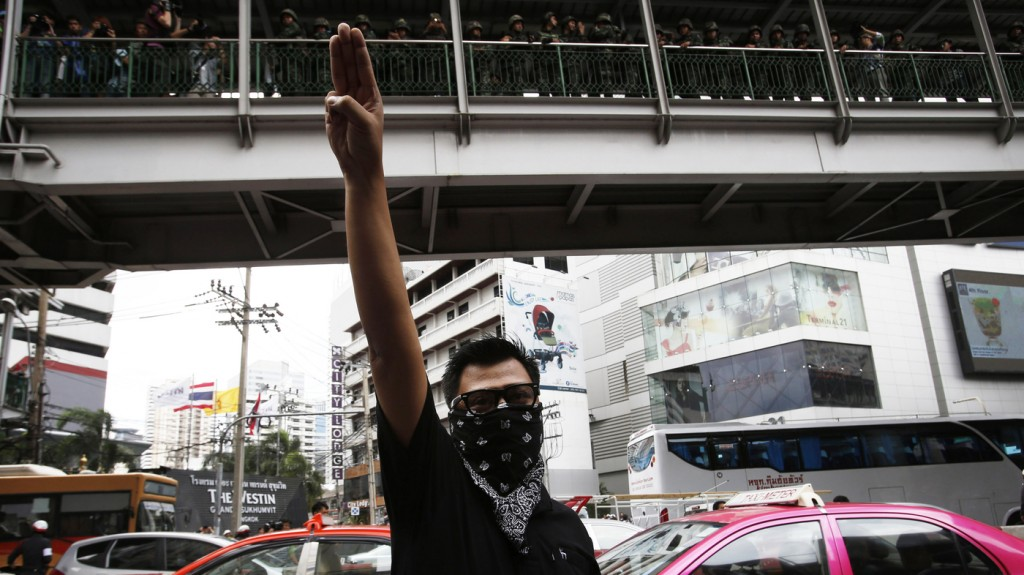 A protester against military rule holds up his three middle fingers as soldiers look on from above during a brief demonstration outside a shopping mall in Bangkok on Sunday. Demonstrators adopted the gesture from The Hunger Games.